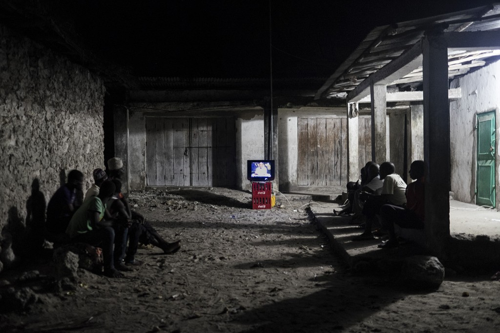 Mmadi watching the news on a TV screen shared with people from his village.