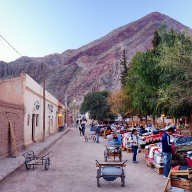Day 69 – Argentina – Purmamarca – The 7 colors mountain in the background of the village market scene at dusk.