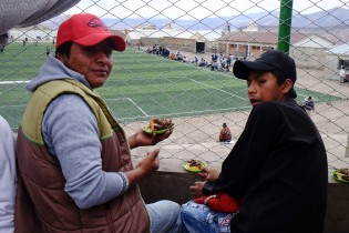 Oscar and his son David, eating some street food (Lllama) in front of a football game.