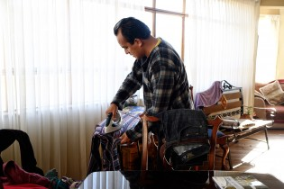 Alvaro at home, ironing his shirt in a hurry before going to work.