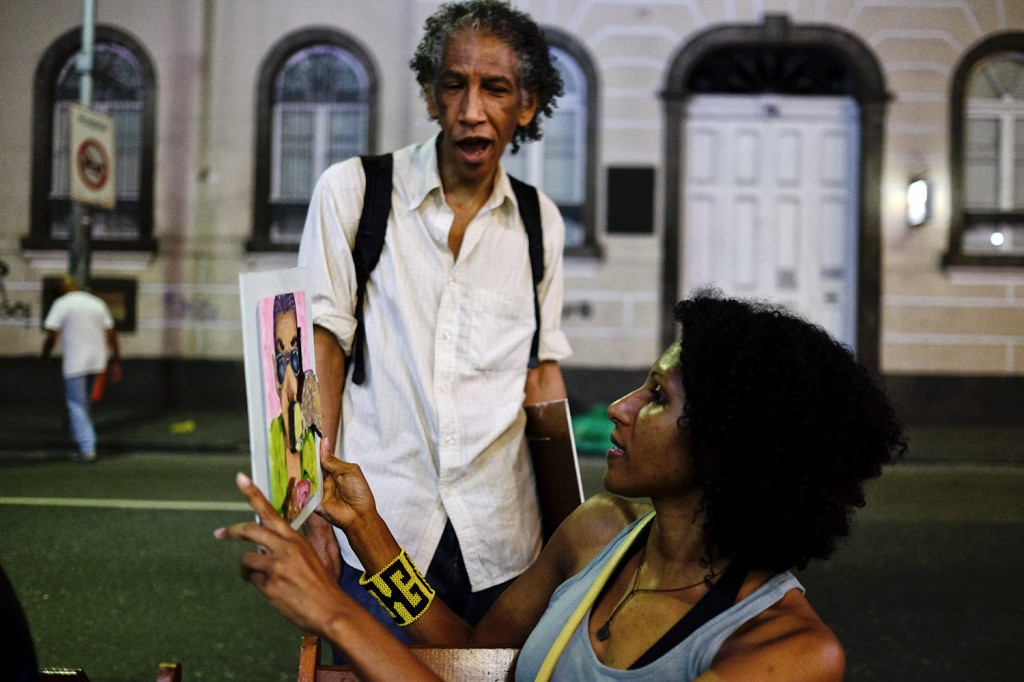 Cristiane talking to an art presenting his work in the streets of Rio de Janeiro.