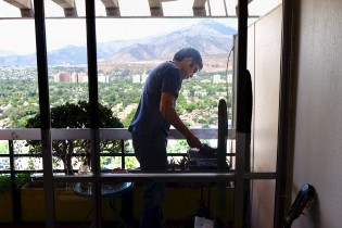 Alvaro preparing a great meat barbeque on the balcony of his apartment.