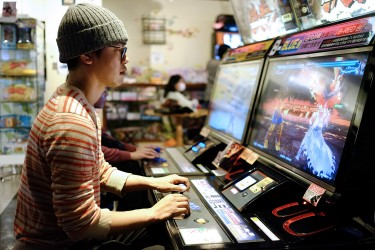 Satoshi playing Tekken 7 at a video game center.
