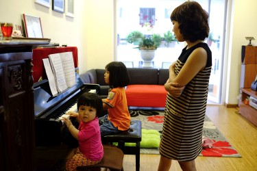 Tung watching over her two daughters will palying piano.