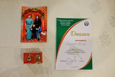 Jibiek chose 3 objects : 1) A picture of her family because they mean everything to her. 2) A pair of earings that symbolizes the Kyrgyz culture. 3) A running certificate that shows her determination.