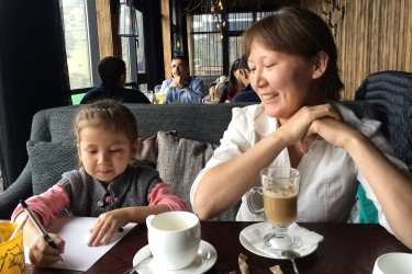 Lazzat and her daughter have a hot drink in shymbulak.